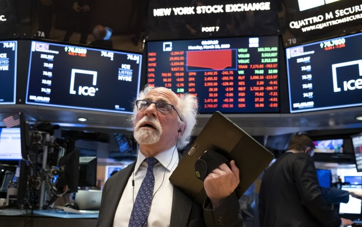 In this March 16, 2020 file photo, trader Peter Tuchman works on the floor of the New York Stock Exchange. Wall Street's plunge into a bear market after a nearly 11-year bull market has been fast and severe, erasing nearly all the S&P 500's gains since Donald Trump's inauguration. The economic disruptions from the coronavirus pandemic and a steep drop in oil prices have many economists forecasting a global recession as early as next month. (AP Photo/Craig Ruttle, File)