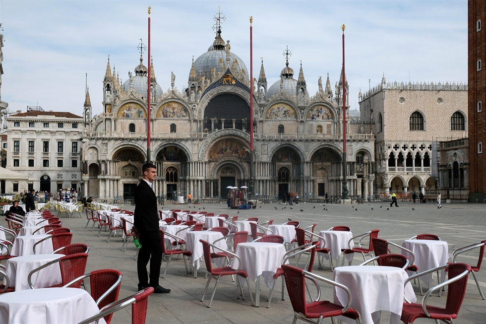 A tourist wearing a mask sits at the tables of a restaurant in front of the Colosseum, in Rome, Italy, March 9, 2020. /EPA