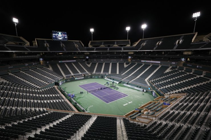 Courtmaster Jeffrey Brooker cleans the center court at the Indian Wells Tennis Garden on Sunday in Indian Wells, California. The BNP Paribas Open was cancelled by the Riverside County Public Health Department, as county officials declared a public health emergency when a case of coronavirus (COVID-19) was confirmed in the area. / AFP-Yonhap