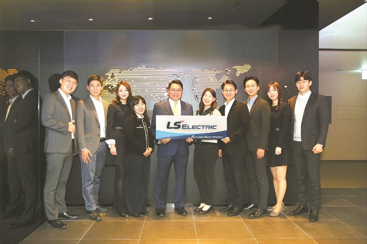 LS Industrial Systems (LSIS) Chairman and CEO Koo Ja-kyun, fifth from left, holds a placard showing the company's new name LS ELECTRIC with employees at LS Tower in Anyang, Gyeonggi Province, Tuesday. / Courtesy of LS ELECTRIC