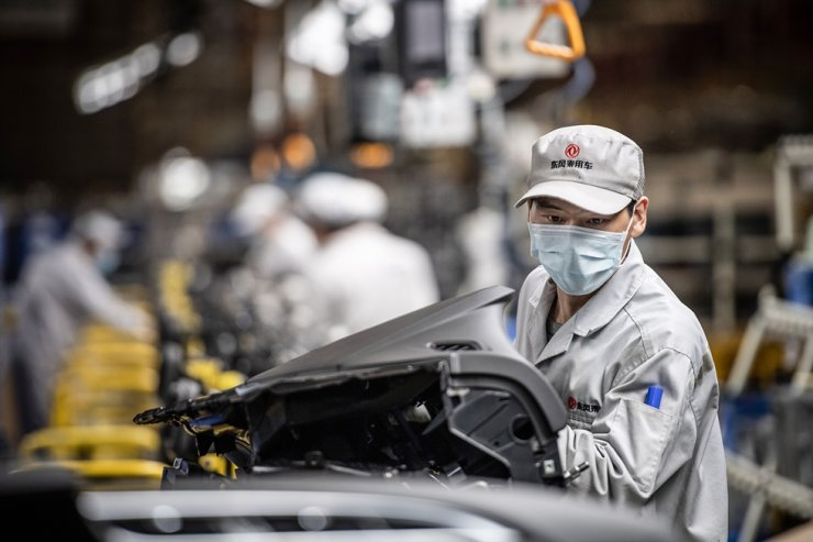This photo taken on March 23, 2020, shows an employee wearing a face mask working on an assembly line at an auto plant of Dongfeng Honda in Wuhan in China's central Hubei province. AFP