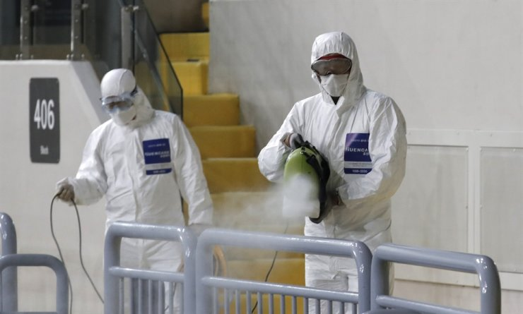 Workers wearing protective gears disinfect as a precaution against the new coronavirus at Gocheok Sky Dome in Seoul, Tuesday, March 17, 2020. AP