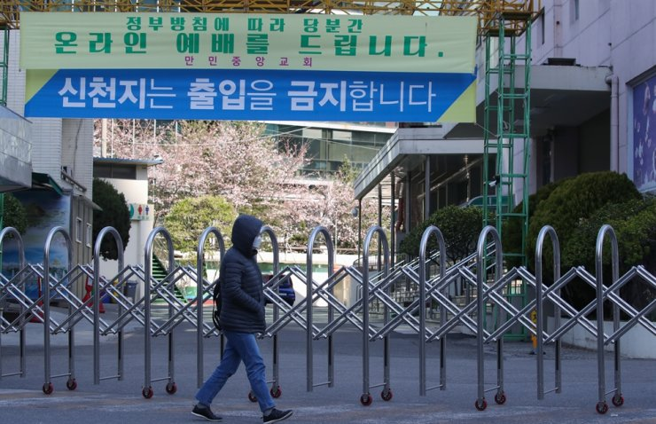 A pedestrian passes by the closed front gate of Manmin Central Church, Guro, Seoul, Sunday, as a number of its members were detected to have been infected by COVID-19. /Yonhap