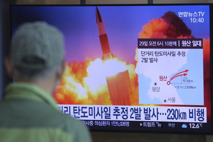 A man watches a news program on a TV at Seoul Station, Sunday, showing a file image of North Korean missile launches. AP-Yonhap
