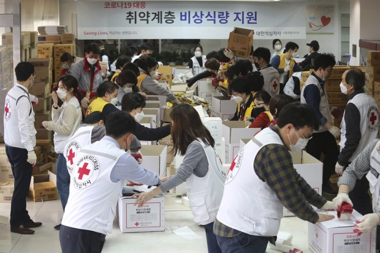 Red Cross workers prepare emergency relief kits packed with basic necessities for delivery to impoverished people experiencing difficulties amid the spread of the new coronavirus at a facility of the Korean National Red Cross in Seoul, Friday, March 27, 2020. AP