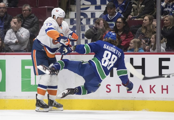 New York Islanders' Matt Martin, left, checks Vancouver Canucks' Adam Gaudette during the first period of an NHL hockey game Tuesday in Vancouver, British Columbia. / AP-Yonhap
