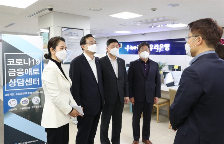 Woori Financial Group Chairman Son Tae-seung, second from left, and Woori Bank CEO Kwon Kwang-seok, third from left, speak with Namdaemun Market merchants at Woori Bank's branch nearby the market in central Seoul, Wednesday. It was Son's first branch visit after he was reappointed as group chairman for a second-term at a shareholders meeting the same day. / Courtesy of Woori Bank