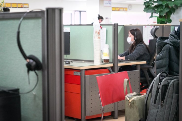 An SKT employee wears a mask while she is on the phone with a customer at the company call center located in Guro, Seoul, Thursday. Courtesy of SKT