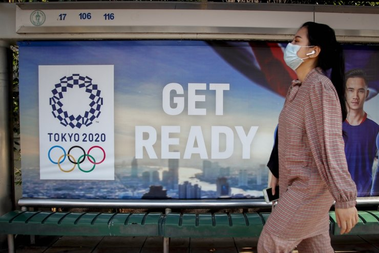 A woman wearing a protective face mask walks past a sign promoting the upcoming Tokyo Olympics at a bus stop in Bangkok, Thailand, Monday. EPA-Yonhap