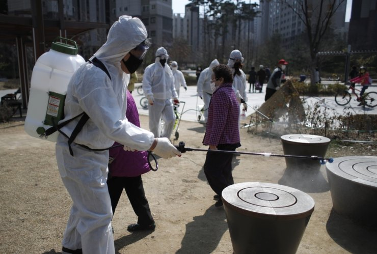 Members of a local residents group wear protective gear as they disinfect a local park as a precaution against the new coronavirus in Seoul, Monday, March 23, 2020. AP