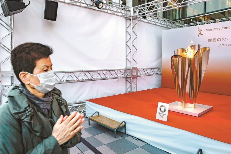 A visitor wearing a face mask looks at the Tokyo 2020 Olympic flame on display outside Sendai railway station in the city of Sendai in Miyagi prefecture on Saturday. / AFP-Yonhap