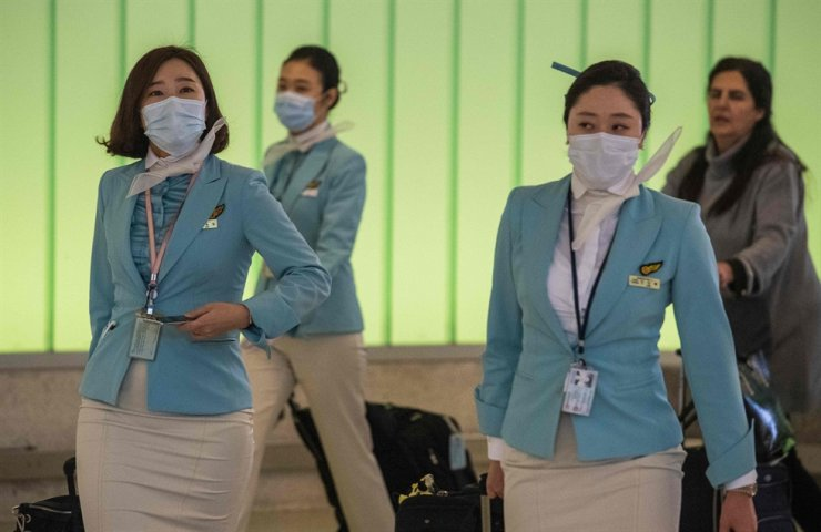 Flight crew from Korean Airlines, wear face masks to protect against the spread of the COVID-19, coronavirus, as they arrive at LAX airport in Los Angeles, California on February 29, 2020. - The US has suffered its first virus related death as the number of novel coronavirus cases in the world rose to 85,919, including 2,941 deaths, across 61 countries and territories. (Photo by Mark RALSTON / AFP)