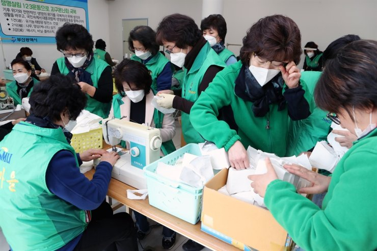 Members of the Saemaul Women's Association make facial masks on their own in Busan, Thursday, amid a serious supply shortage caused by the rapid spread of COVID-19 nationwide. About 10,000 masks they produced will be provided to needy neighborhoods. / Yonhap
