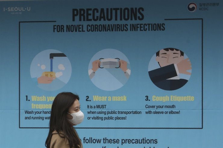 A woman wearing a face mask passes by a poster about precautions against the new coronavirus in Seoul, Thursday, March 26, 2020. AP