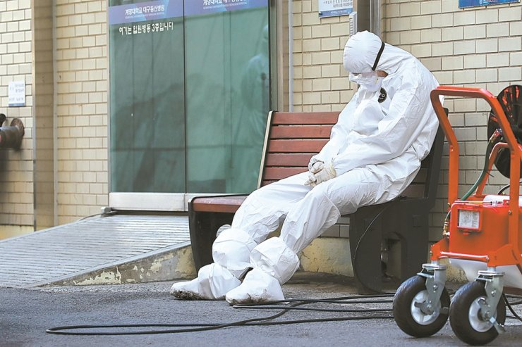 An exhausted medical worker wearing full protective suit rests on a chair after treating COVID-19 patients at Keimyung University Dongsan Medical Center in Daegu, in this Feb. 23 file photo. /Yonhap