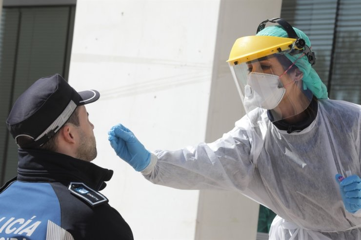 A handout picture released by the Madrid City Hall shows a health worker handling a swab to test a municipal police officer for the COVID-19 virus in Madrid on March 25, 2020. AFP