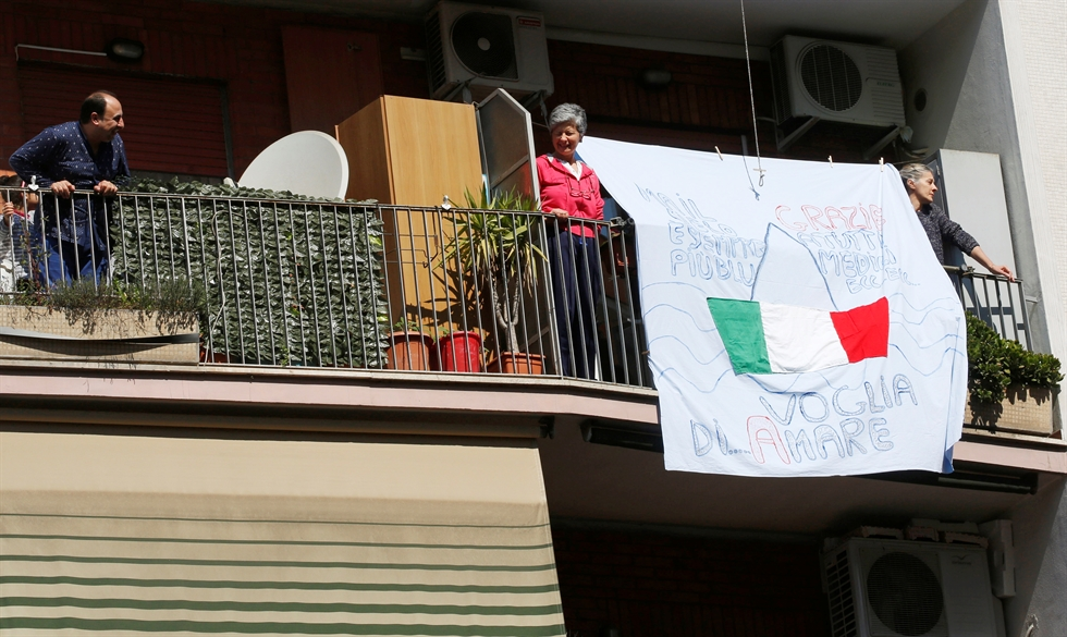 A woman looks on from her window as radio stations across the country play the Italian national anthem for a flash mob to raise spirits while Italy remains under lockdown to prevent the spread of COVID-19 in Rome, Italy, March 20, 2020. Reuters