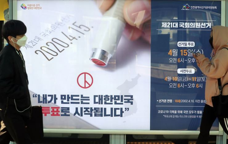 A citizen passes by a promotional booth for the General Election in Incheon, March 23. Yonhap