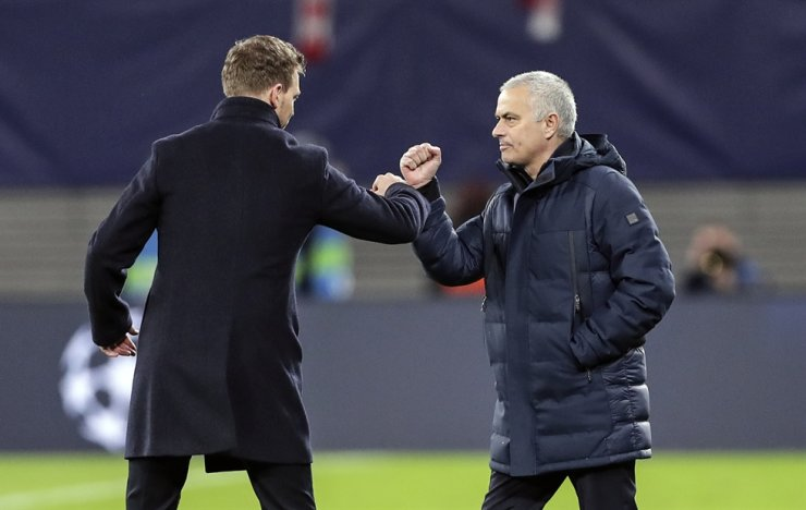 Tottenham's manager Jose Mourinho, right, and Leipzig's head coach Julian Nagelsmann touch their forearms instead of shaking hands due to the coronavirus after the Champions League round of 16, 2nd leg football match between RB Leipzig and Tottenham Hotspur in Leipzig, Germany, Tuesday. Leipzig defeated Tottenham with 3-0. / AP-Yonhap