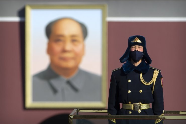 In this Tuesday, Feb. 4, 2020 file photo, a member of an honor guard wears a face mask as he stands guard in Tiananmen Square in Beijing. Wednesday, March 17, 2020. AP