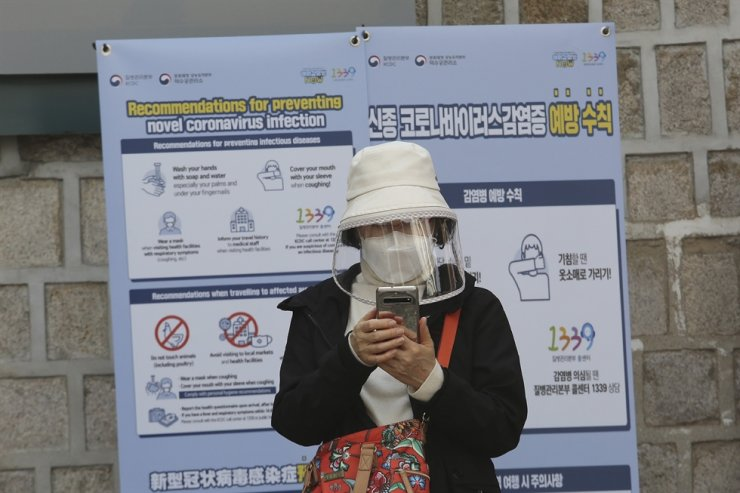 A woman wearing a face mask watches her smartphone in Seoul, Saturday, March 21, 2020. AP