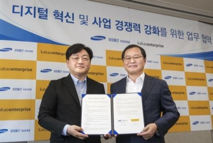 Baek Sang-yeop, CEO of Kakao Enterprise, left, and Samsung C&T CEO Chung Keum-yong signs business cooperation agreement to implement AI technology at Everland. Courtesy of Samsung C&T