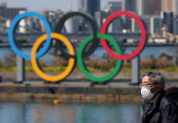 A man wearing a face mask, following an outbreak of the coronavirus, walks in front of giant Olympic rings at the waterfront area at Odaiba Marine Park in Tokyo, Japan, March 6. /Reuters