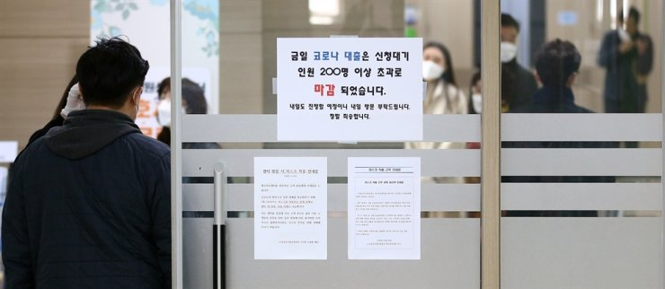 In this March 4 photo, a sign on the door of the Daegu Small Enterprise and Market Service says it cannot process any new coronavirus-related hardship loan applications for the day as the daily limit of 200 had already been lodged. Yonhap