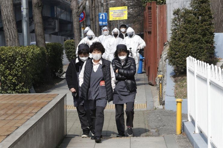 Women wearing face masks walk as South Korean army soldiers spray disinfectant as a precaution against a new coronavirus on a street in Seoul, Monday, March 9, 2020. AP