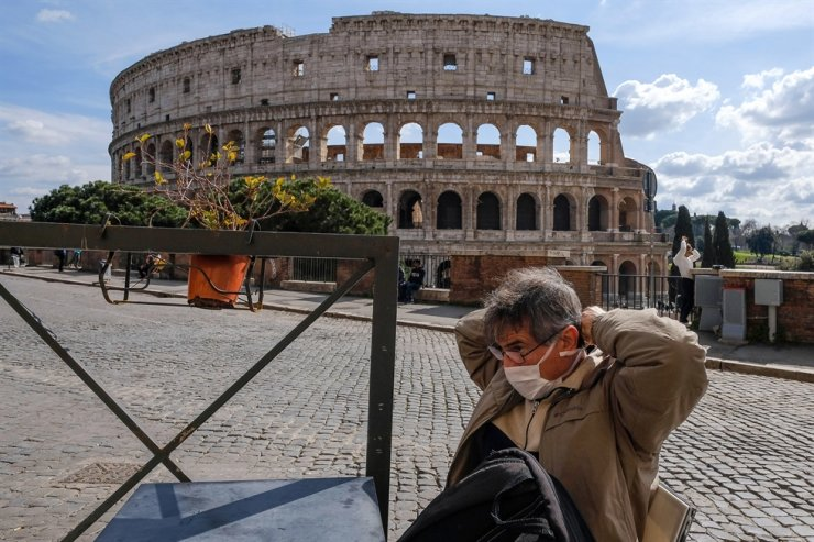 A tourist wearing a mask sits at the tables of a restaurant in front of the Colosseum, in Rome, Italy, March 9, 2020. EPA
