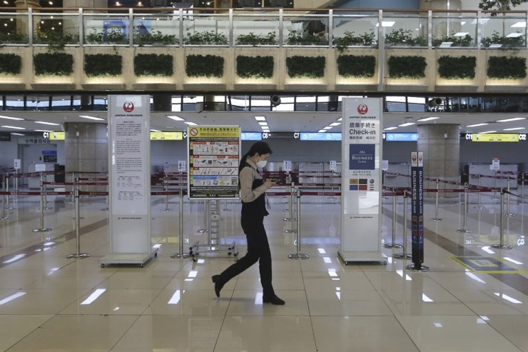 A Gimpo Airport official wearing a face mask passes by check-in counters of Japan Airlines at Gimpo Airport in Seoul, Monday, March 9, 2020. Korea announced it will end visa-free entry for Japanese citizens starting Monday in retaliation for a two-week quarantine imposed by Japan on all visitors from Korea because of its surging viral outbreak. AP