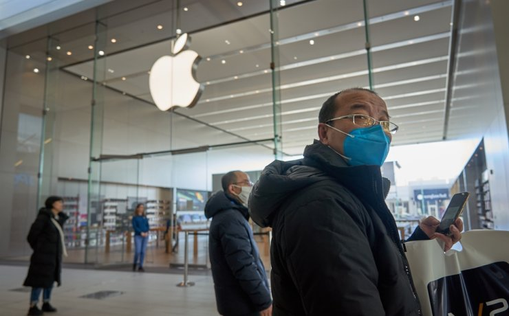 People in face masks walk past an Apple store in Brossard, on the south shore of Montreal, Canada, March 15. The people in the photo are unrelated to the story. EPA