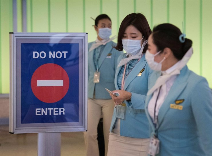 Flight crew from Korean Airlines, wear face masks to protect against the spread of the COVID-19, coronavirus as they arrive at LAX airport in Los Angeles, Calif., Feb. 29, 2020. AFP
