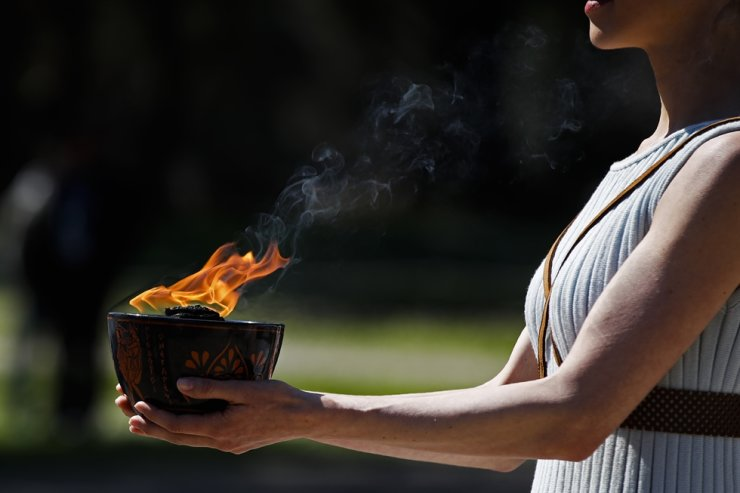 An actress, playing the role of the priestess, holds the flame during the flame lighting ceremony at the closed Ancient Olympia site, birthplace of the ancient Olympics in southern Greece, March 12. The Olympic flame from Greece is set to arrive in Japan even as the opening of the Tokyo Games in four months is in doubt with more voices suggesting the games should to be postponed or canceled because of the worldwide virus pandemic. / AP-Yonhap