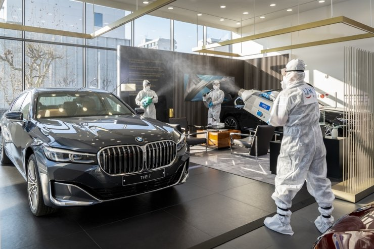 CESCO workers disinfect a BMW facility and car displayed in the showroom in Seoul, on March 24. / Courtesy of BMW Korea