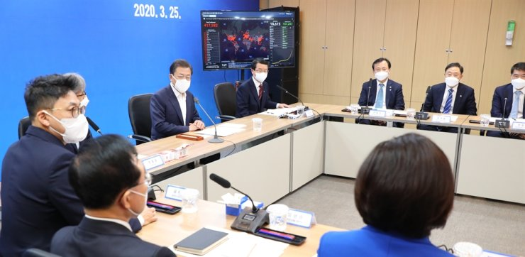 President Moon Jae-in speaks with representatives of Korean COVID-19 detection kit makers, including SolGent's co-CEO You Jae-hyung, left, at Seegen's office in southern Seoul, Wednesday. Yonhap