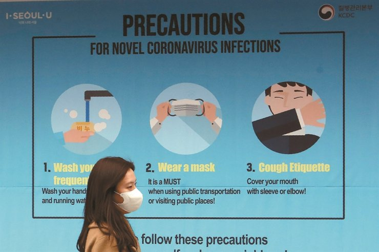 A woman wearing a face mask passes by a poster about precautions against the new coronavirus in Seoul, South Korea, Thursday. For most people, the new coronavirus causes mild or moderate symptoms, such as fever and cough that clear up in two to three weeks. For some, especially older adults and people with existing health problems, it can cause more severe illness, including pneumonia and death. /AP-Yonhap