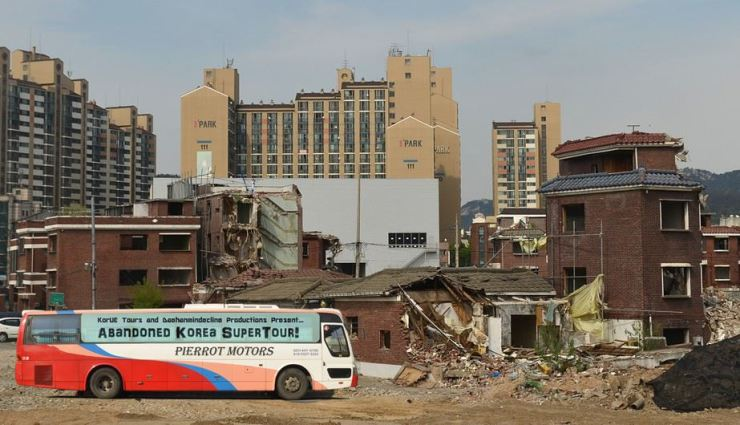 A manipulated image shows a tour bus passing through a Seoul urban renewal zone. The image was intended to emphasize the exploitative nature of poverty tourism./ Courtesy of Ron Bandun