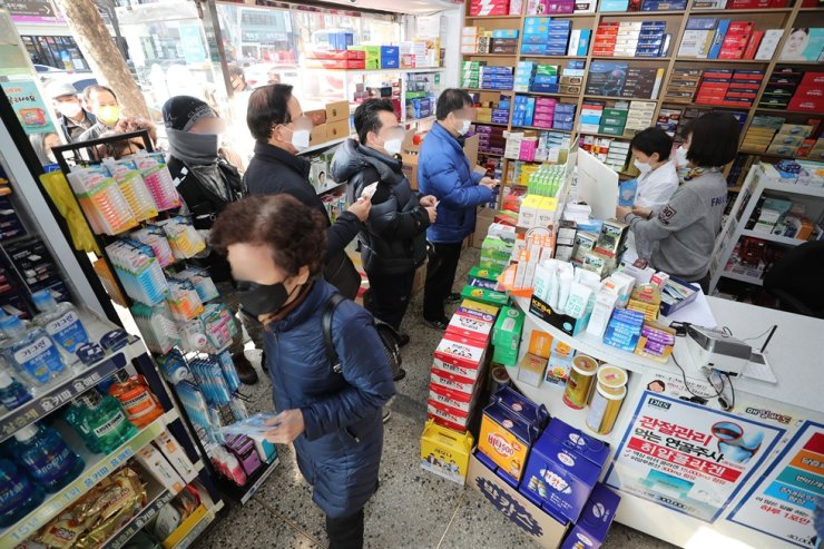 People line up to buy masks at a pharmacy in Jongno District, Seoul, Friday. /Yonhap
