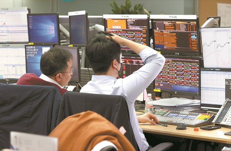 Dealers at Hana Bank watch monitors in a dealing room at its office in Seoul, Tuesday. The benchmark KOPSI closed at 1,672.44, down 2.47 percent from the previous trading day. The won-dollar exchange rate also surged to close at 1,243.5 won per U.S. dollar, up 17.5 won from a day earlier. Yonhap