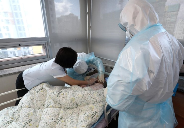 Health workers perform a coronavirus test on an elderly patient at a nursing home in Gangnam, Seoul. Courtesy of Gangnam District Office