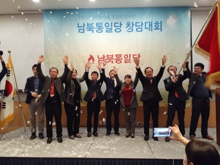 Officials of the Unification Party of North and South Koreas, a new political party launched by North Korean defectors, cheer during an inauguration ceremony at the Federation of Korean Industries Tower in Seoul, March 6. Fourth from left is Ahn Chan-il and fifth from left, Kim Seong-min, who were elected co-leaders of the party. Courtesy of the Unification Party of North and South Koreas