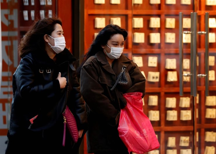 Pedestrians wearing masks make their way through a shopping district in virus-hit Daegu, Korea, March 4. Reuters