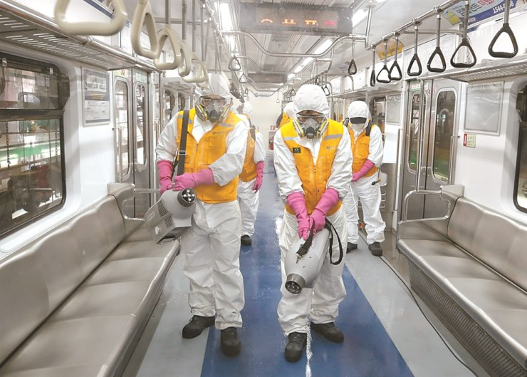 Workers wearing protective gears disinfect a subway car as a precaution against the new coronavirus in Seoul, South Korea, Wednesday. AP-Yonhap