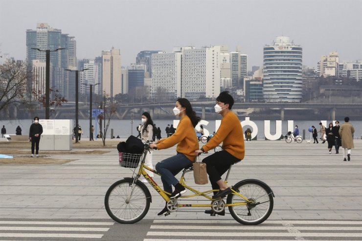 A couple wearing face masks rides a bicycle at a park in Seoul, Saturday, March 7, 2020. AP
