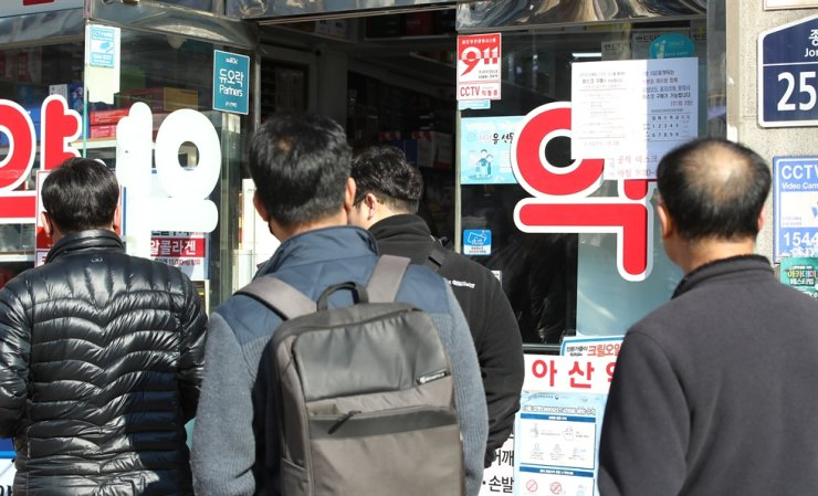 People line up to buy masks outside a pharmacy in Jongno, Seoul, Monday./ Yonhap