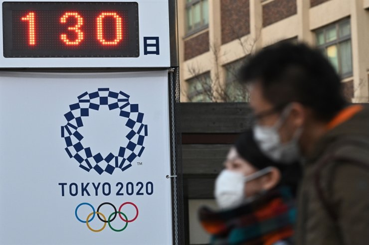 Pedestrians wearing face masks walk past a board showing the number of days to the Tokyo 2020 Olympic Games in Yokohama on March 16, 2020. Doubts are growing in Japan about the Tokyo Olympics, with growing opposition to holding them as scheduled and some urging officials not to risk lives by pressing ahead during the coronavirus emergency. AFP