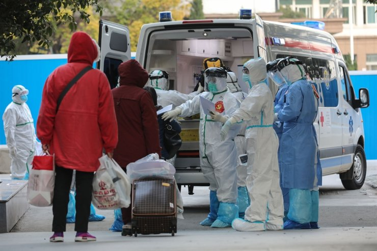 A medical staff member checks information as patients infected by the COVID-19 coronavirus leave from Wuhan No.3 Hospital to Huoshenshan Hospital in Wuhan in China's central Hubei province on March 4, 2020. - China on March 4 reported 38 more deaths from the new coronavirus but a fall in fresh cases for a third consecutive day. (Photo by STR / AFP)