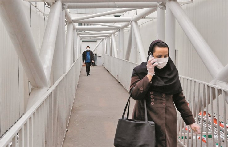 A woman wearing a protective face mask and plastic gloves uses her phone while walking along a pedestrian overpass bridge in Iran's capital Tehran on March 14, 2020. /AFP-Yonhap