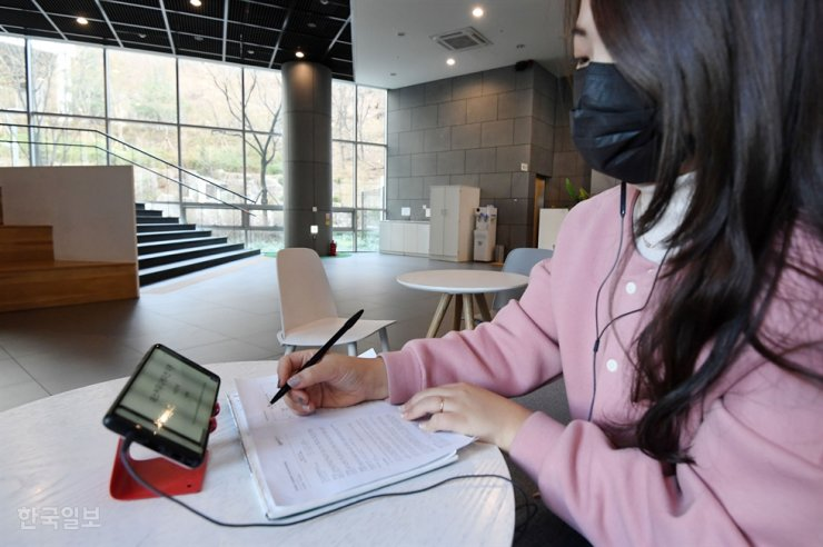 A student listens to an online lecture at a cafe, Seoul, March 16, as schools delayed their opening of spring semester due to COVID-19. Korea Times file